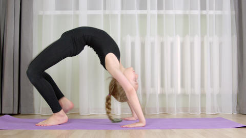 Flexible girl training acrobatic exercise in home. Acrobat girl bending to Live Action
