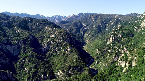 Aerial view of green mountain mountain peak with beautiful blue sky Live Action