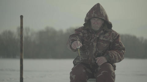 Winter fishing. Man fisherman catches fish in winter Live Action