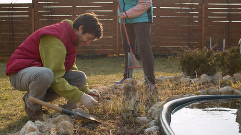 Family prepares flowerbed for spring planting Live Action