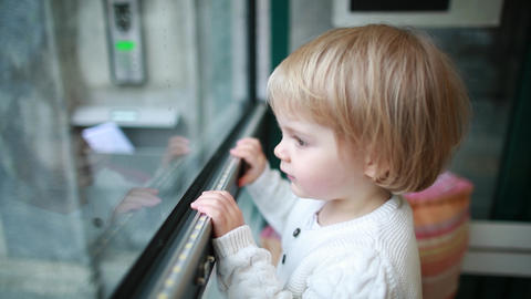 Adorable blond child looks with interest into a large window from the room Live Action