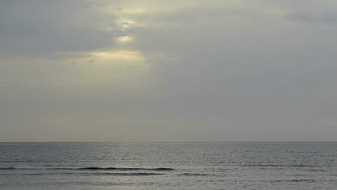 Sun hiding behind gray clouds in gloomy sky over endless sea surface. Timelapse Footage