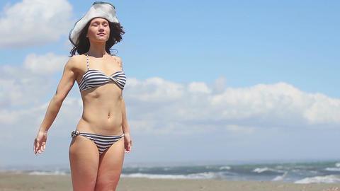 Pretty woman in bikini and hat standing on sandy beach, suntanning near sea Footage