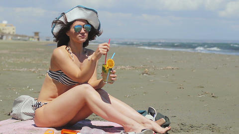 Sexy lady in bikini drinking cocktail, enjoying rest on sandy beach at seaside Footage