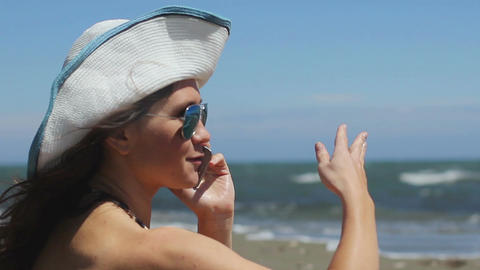 Excited young woman on beach talking emotionally on phone, waving hands, smiling Footage