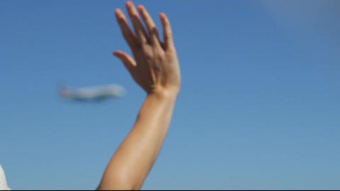 Woman looking at landing airplane, waving hand to welcome new tourists arrival Footage