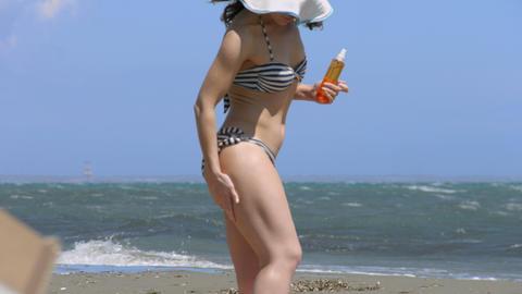 Hot female rubbing hips, applying sunscreen spray, suntanning on summer beach Footage