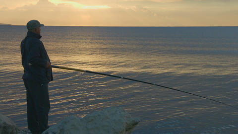 Elderly man fishing with rod from a rocky ocean shore, active rest, magic hour Footage