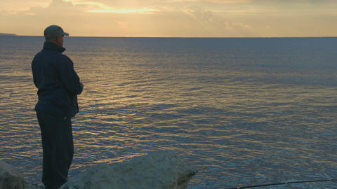 Fisherman throwing stones into water at sunrise, sunset. Magic hour, relaxation Footage