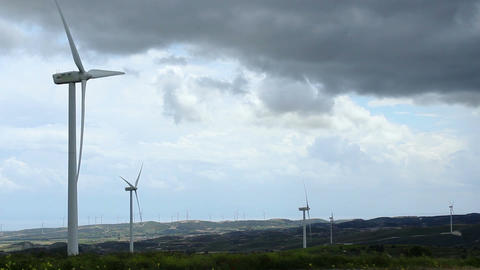 Time-lapse of wind turbine propellers rotating in green field, dark cloudy sky Footage