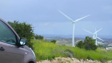 Electric car, wind turbines rotating, green energy source, clean environment Live Action