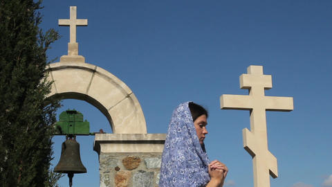 Religious woman praying to God. Monastery, stone crosses, solitude, spirituality Footage