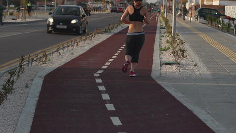 Fit woman running a jogging track along city street, outdoor fitness, sportswear Live Action