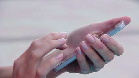 Closeup shot of female hands holding smartphone, typing text on touch screen Footage