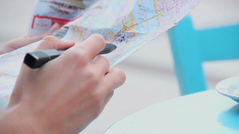 Closeup of female hands holding map, writing notes, checking route during trip Footage
