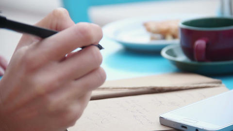 Hands of woman writing in notebook, cup of coffee, smartphone on cafe table Footage
