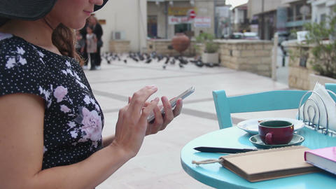 Female sitting at street cafe table, using smartphone, typing message, scrolling Footage