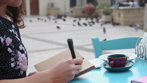 Young brunette at resort writing a diary, journalist, writer making notes Footage