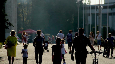Silhouettes of adults and children riding bicycles, families with baby strollers Footage
