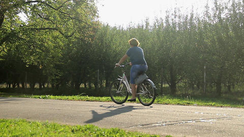 Overweight woman riding bicycle. Obesity problem. Weight loss activities Footage