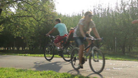 Children and parents riding bicycles on bikeway in public park. Active leisure Footage