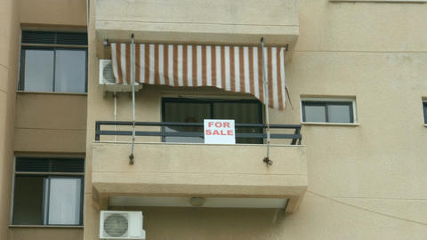 For sale sign on apartment balcony. Real estate agency services. Debt crisis Live Action