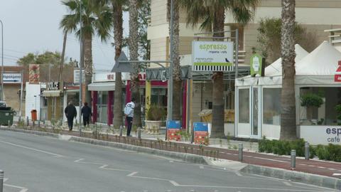 Empty resort town street at low season. Few local people walking on sidewalk Footage
