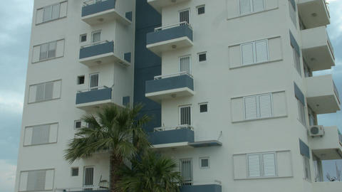 Establishing shot of multi-storey apartment building in exotic country. Realty Footage