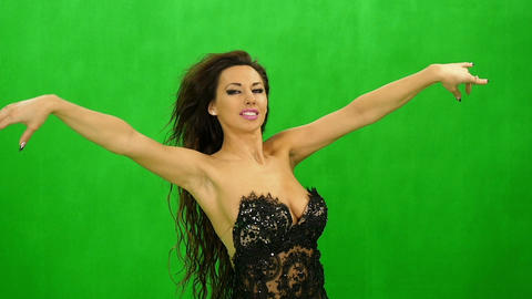 A young woman in black dress dancing & smiling on green background Footage