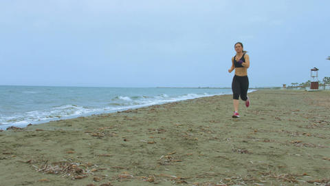 Female athlete training at seaside, running on sandy beach. Success motivation Footage
