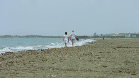 Elderly couple walking along stormy sea. Waves splashing on empty sandy beach Footage