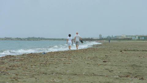 Elderly couple walking along stormy sea. Waves splashing on empty sandy beach Footage