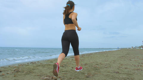 Young woman running at seaside, living active lifestyle for healthy fit body Footage