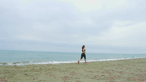 Beautiful girl jogging along sea. Salty waves splashing on empty sandy beach Footage