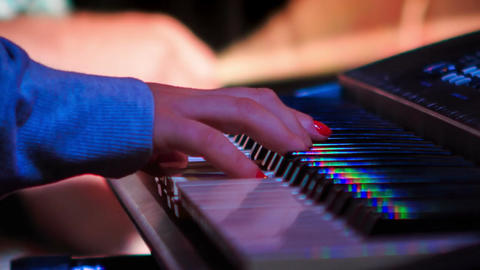 Girl Plays Electric Piano in Night Bar under Light Flashes Footage
