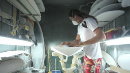 Surfboard making, shaper sanding the bottom of the surfboard Footage
