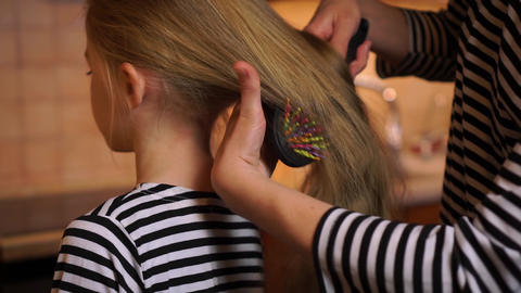 Careful mother brush comb daughter child long hair with colorful comb brush wearing striped dress at Live Action