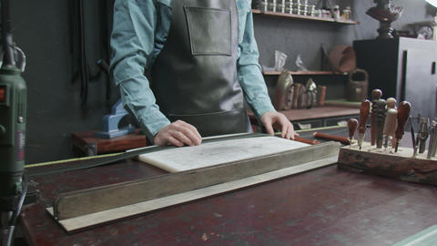 The tanner picks up a tools for working with leather. Many different tools for Live Action