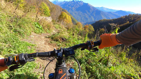 Point view from action camera hands of rider on bicycle handlebar while riding on autumn mountain Live Action