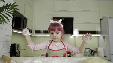 Cooking pizza. Little child playing with flour gets her hands dirty in kitchen Live Action