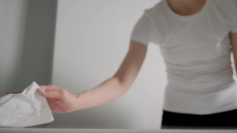 Slow motion: woman cleaning white table with wet wipe - disinfection concept Live Action
