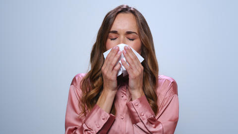 Sick businesswoman sneezing in studio. Ill woman using napkin on blue background Live Action