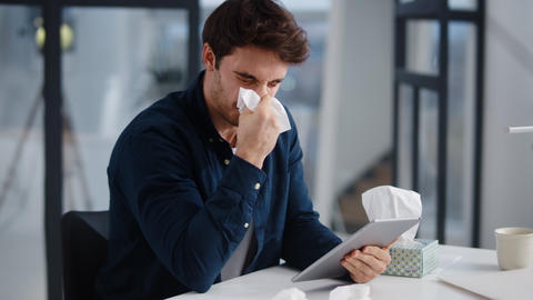Sick business man getting flu in office. Ill man sneezing near laptop indoor Live Action