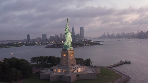 AERIAL: Circling Statue of Liberty beautifully illuminated in early morning Live Action