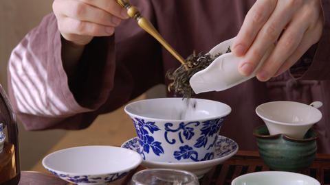 Close up view of male hands pouring tea leaves in tea bowl GIF