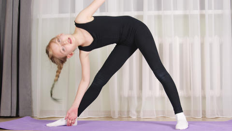 Concentrated sporty teen girl practicing yoga at home Live Action