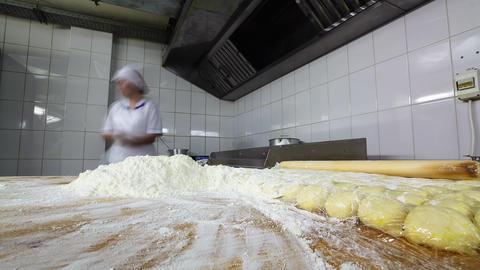 skilled baker works making tasty buns in bakery workshop Live Action