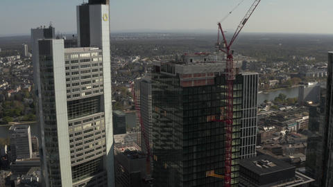 AERIAL: Close Up View of Skyscraper construction site in Urban environment with Live Action