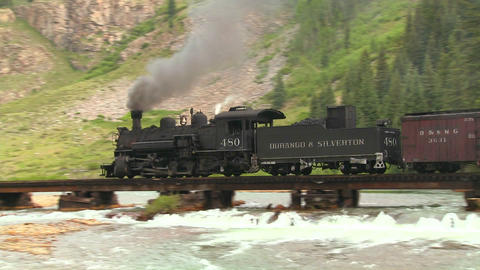 A beautiful shot of a steam train crossing a bridg Footage