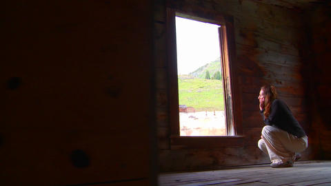 A woman sits in an abandoned house looking out the Footage